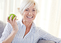 Woman holding apple and smiling about dental implants in Irving,TX