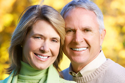 Man and woman smiling about their dental implants in Irving,TX
